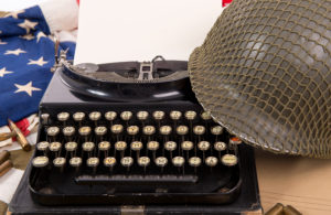 Historic US military helmet of the Second World War with old typewriter