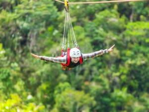 Men enjoying zip-line flying over the forest at Gunstock Mountain