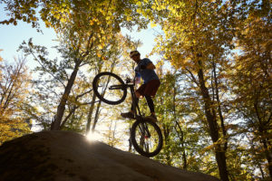 mountain biking cyclist balancing on back wheel on boulder in sunny forest