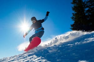 Snowboarder Riding Red Snowboard on sunny day on Gunstock Mountain