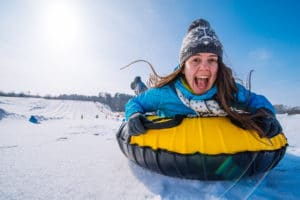Young Smiling Woman while tubing on a sunny day at Gunstock Mountain