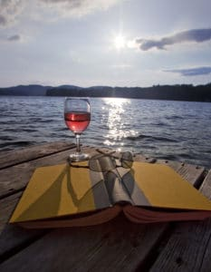 Glass of red wine, book, and sunglasses on dock at lake in the Lakes Region NH